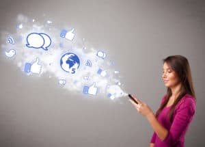 Woman holding a phone with social media icons in an abstract cloud