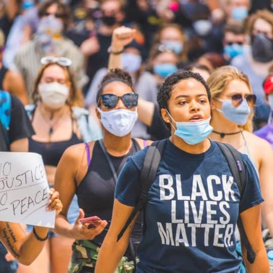 A young woman wearing a mask and black lives matter t-shirt marching in a #BlackLivesMatter public demonstration in Cincinnati.
