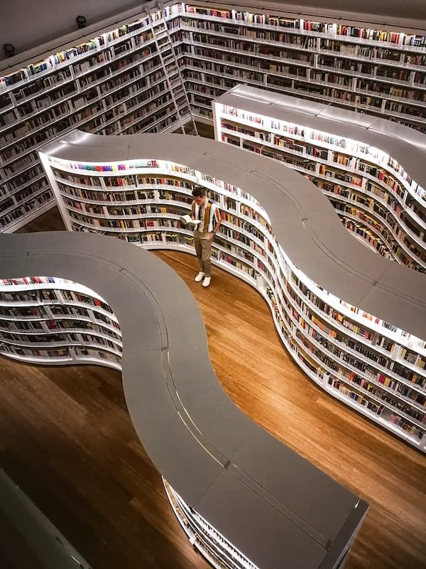 Man browsing in winding bookstore shelves