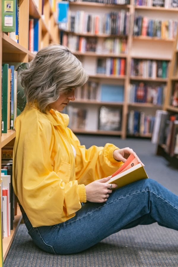 Woman in bookstore reading books every marketer should read