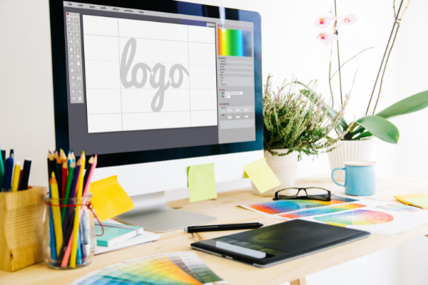 Computer displaying logo graphic design program with colour samples on desk