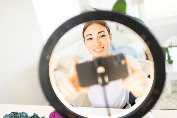 Woman setting up smartphone camera with ring light