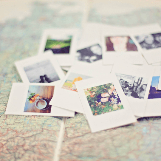 Pile of instant photos lying on map