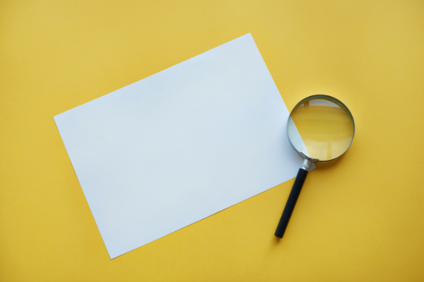 Piece of paper and magnifying glass on yellow background
