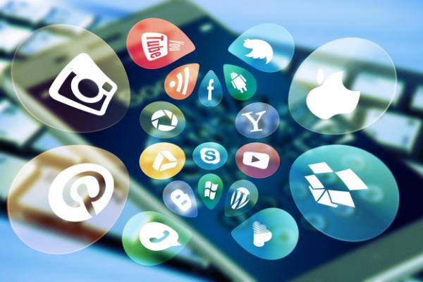 Smartphone and keyboard displaying social media platform symbols