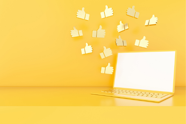 Yellow laptop on yellow background with social media thumbs up symbols