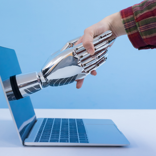 Robot hand reaching out of computer screen to shake human hand