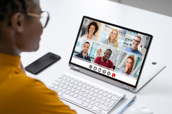 Woman attends virtual meeting with six attendees on computer screen