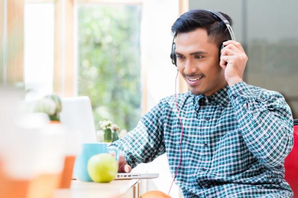 Man smiles at laptop computer while wearing headphones