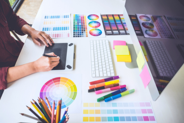 Graphic designer with colour swatches, computer and tablet on desk
