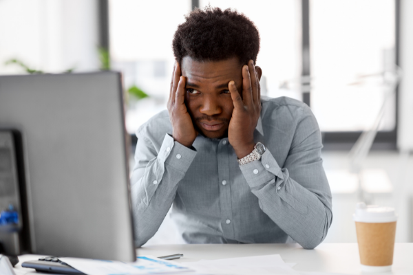 Man with inbox fatigue sitting at desk with computer