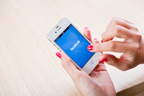 Hands with red nail polish holding smartphone displaying Facebook logo