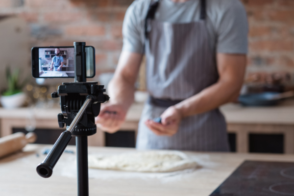 Man filming cooking explainer video with smartphone in kitchen