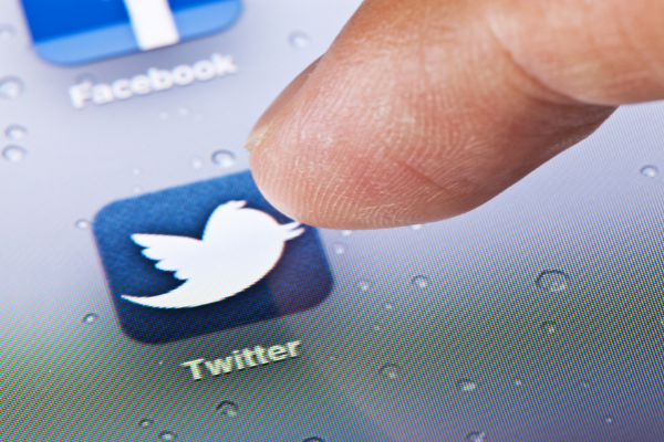 Finger points to Twitter app icon on screen
