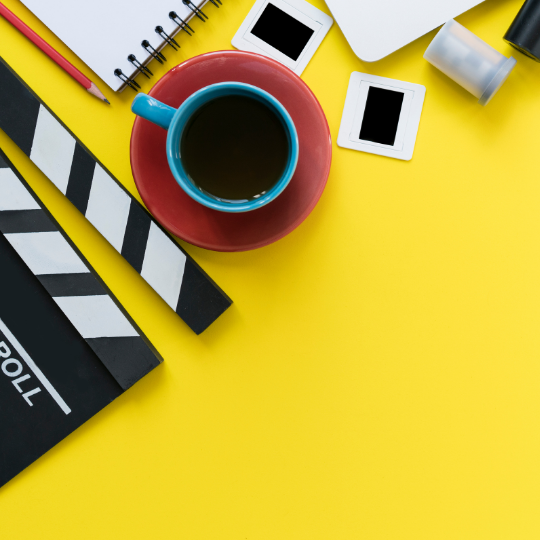Clapperboard and filmmaking supplies on yellow background